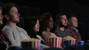 Vrienden die in bioskoop op een film letten stock footage