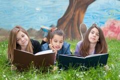 Vrienden die boeken lezen Stock Afbeeldingen