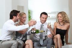 Vrienden die champagne drinken Stock Afbeeldingen