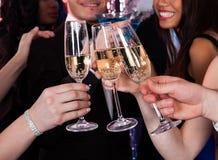 Vrienden die champagne roosteren bij nachtclub Royalty-vrije Stock Foto's