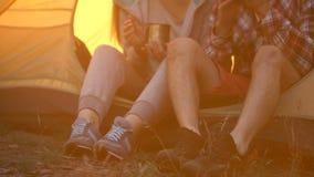 Vrienden die in comfortabele schoenen in tent en het drinken thee zitten, die in bos wandelen stock video