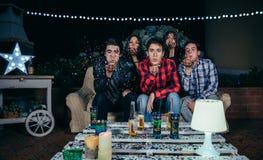 Vrienden die confettien blazen aan de camera in partij royalty-vrije stock foto