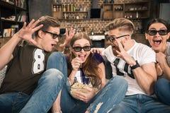 Vrienden die in 3D glazen op film letten Stock Foto