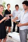Vrienden die de champagne knallen stock afbeeldingen