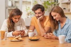 Vrienden die in de keuken zitten en op hun telefoons letten op stock afbeeldingen