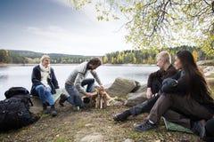 Vrienden die de Mens bekijken die Vuur bij Oever van het meer het Kamperen voorbereiden royalty-vrije stock afbeeldingen