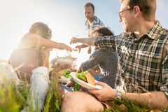 Vrienden die de zomerbbq picknick hebben en samen eten royalty-vrije stock afbeeldingen