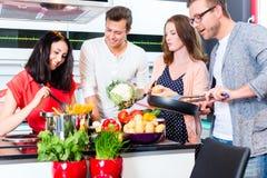 Vrienden die deegwaren en vlees in binnenlandse keuken koken Royalty-vrije Stock Afbeeldingen