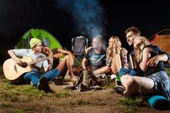 Vrienden die dichtbij vuur, het glimlachen, het omhelzen, het rusten, het spelen gitaar zitten camping stock afbeelding