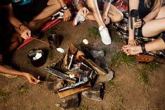 Vrienden die dichtbij vuur, het glimlachen, het spelen gitaar zitten Het kamperen grillheemst Royalty-vrije Stock Afbeeldingen