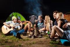 Vrienden die dichtbij vuur, het glimlachen, het spreken, het rusten, het spelen gitaar zitten camping royalty-vrije stock fotografie