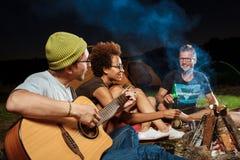 Vrienden die dichtbij vuur, het glimlachen, het spreken, het rusten, het spelen gitaar zitten camping stock fotografie