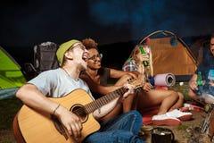 Vrienden die dichtbij vuur, het glimlachen, het spreken, het rusten, het spelen gitaar zitten camping royalty-vrije stock foto