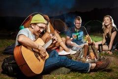 Vrienden die dichtbij vuur, het glimlachen, het spreken, het rusten, het spelen gitaar zitten camping stock afbeeldingen