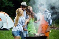Vrienden die een barbecuepartij in aard hebben royalty-vrije stock foto