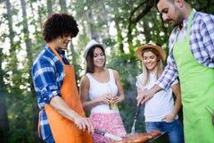 Vrienden die een barbecuepartij in aard hebben terwijl het hebben van pret royalty-vrije stock afbeeldingen