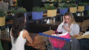 Vrienden die een onderbreking hebben en smartphones bij een koffie in wandelgalerij na het winkelen gebruiken stock video