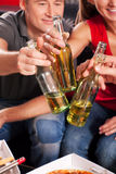 Vrienden die een partij hebben en flessen clinking Stock Foto's