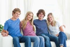Vrienden die elkaar houden aangezien zij de camera bekijken Stock Foto's