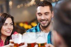 Vrienden die en bier drinken bij restaurant dineren Stock Foto's
