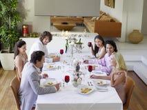 Vrienden die en bij Dinerpartij drinken socialiseren stock fotografie