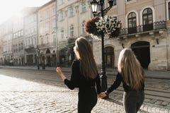 Vrienden die en in de oude stad glimlachen lopen stock afbeelding