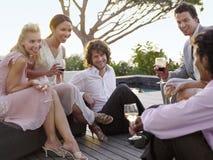 Vrienden die en op Portiek drinken socialiseren Stock Foto's