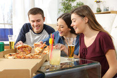 Vrienden die en pizza thuis spreken eten Stock Foto