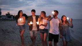 Vrienden die, en pret hebben tijdens nachtpartij bij de kust met het sterretjelichten van Bengalen dansen in hun handen lopen stock video