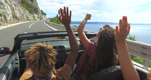 Vrienden die en wapens golven die op weg langs kust in rode convertibel drijven dansen stock footage