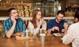 Vrienden die en wijn drinken bij restaurant dineren stock foto