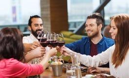 Vrienden die en wijn drinken bij restaurant dineren Stock Afbeelding