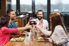 Vrienden die en wijn drinken bij restaurant dineren royalty-vrije stock afbeeldingen