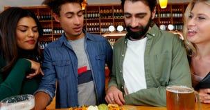 Vrienden die glas bier en Mexicaans voedsel in bar 4k hebben stock video