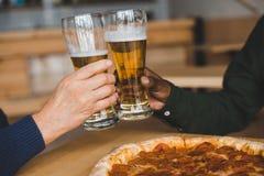 Vrienden die glazen bier clinking Royalty-vrije Stock Afbeelding
