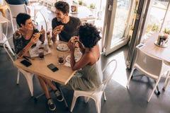 Vrienden die hamburger hebben bij restaurant Stock Fotografie
