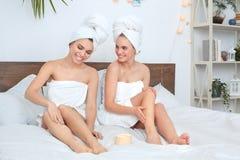 Vrienden die handdoeken samen thuis schoonheidsverzorging dragen die toepassend lichaamslotion vrolijk spreken liggen royalty-vrije stock afbeeldingen