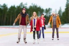 Vrienden die handen op openlucht het schaatsen piste houden Stock Afbeelding