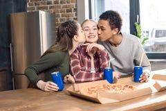Vrienden die het glimlachen tiener` s wangen kussen, die pizza thuis concept eten Royalty-vrije Stock Foto's