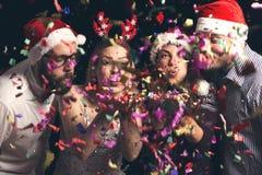 Vrienden die kleurrijke confettien wegblazen stock foto's