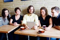 Vrienden die koffie en computer van toegang genieten stock foto