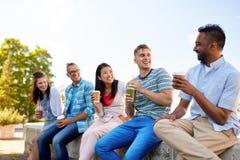 Vrienden die koffie en sap drinken die in stad spreken stock foto's