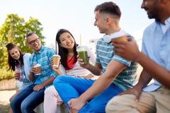 Vrienden die koffie en sap drinken die in stad spreken stock fotografie