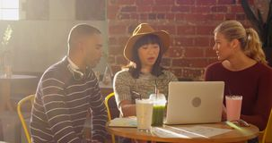 Vrienden die laptop met behulp van terwijl het hebben van drank 4k stock videobeelden