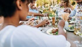 Vrienden die lunch hebben samen bij in openlucht restaurant Stock Foto's