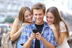 Vrienden die media in een slimme telefoon delen Stock Afbeeldingen