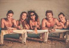 Vrienden die met dranken op een strand ontspannen royalty-vrije stock foto