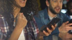 Vrienden die met smartphones voor de overwinning van het sportenteam in bar toejuichen, die online wedden stock videobeelden