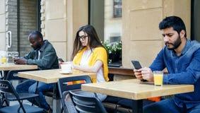 Vrienden die met Smartphones zitten royalty-vrije stock foto