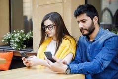 Vrienden die met Smartphones zitten stock foto's